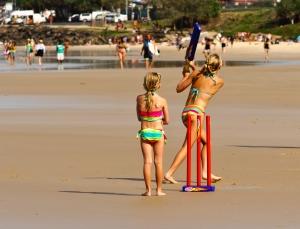 A family plays beach cricket at Byron Bay