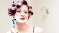 Beautiful funny girl shaving with foam & razor her face