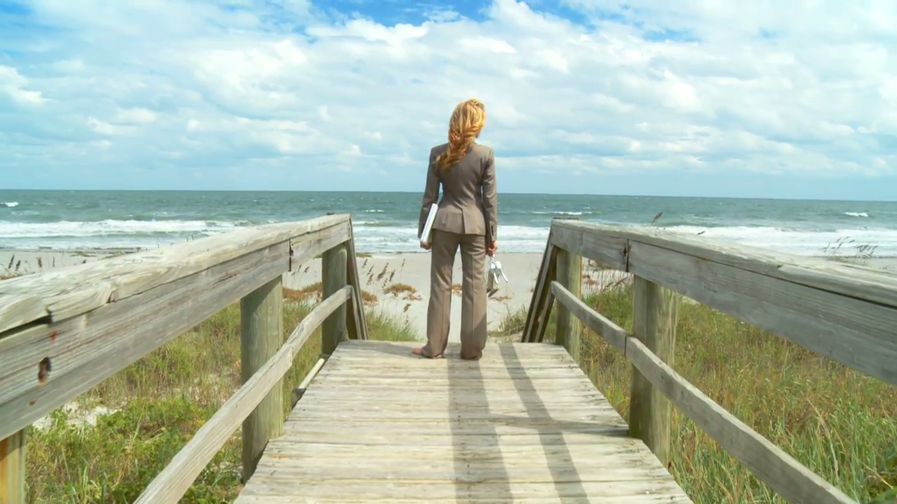 beautiful-blonde-businesswoman-using-technology-to-work-from-the-beach-60-fps_n1xjfhjr1g__F0000